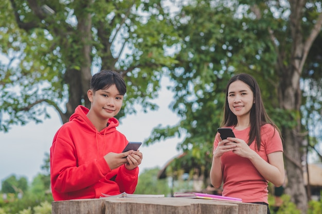 Asian women with lady boy lgbt are using mobile smartphone search learning study class online technology, back to school education concept