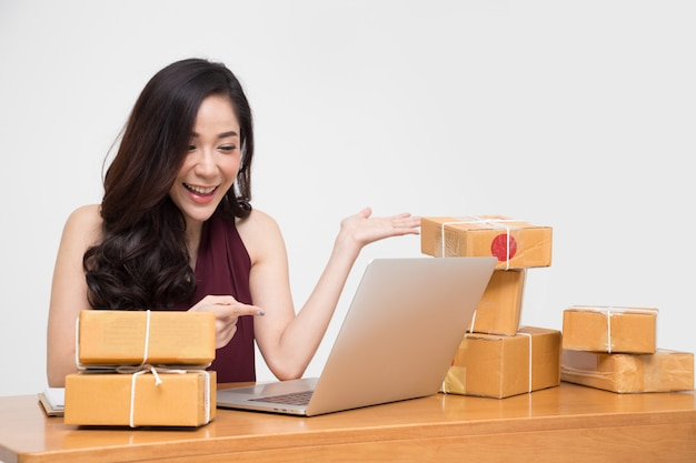Asian women with parcel box on table in conversation with customer.