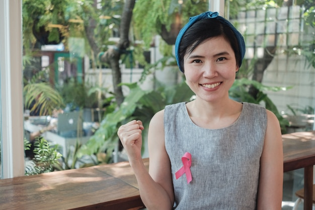 Asian women with pink ribbon, breast cancer awareness