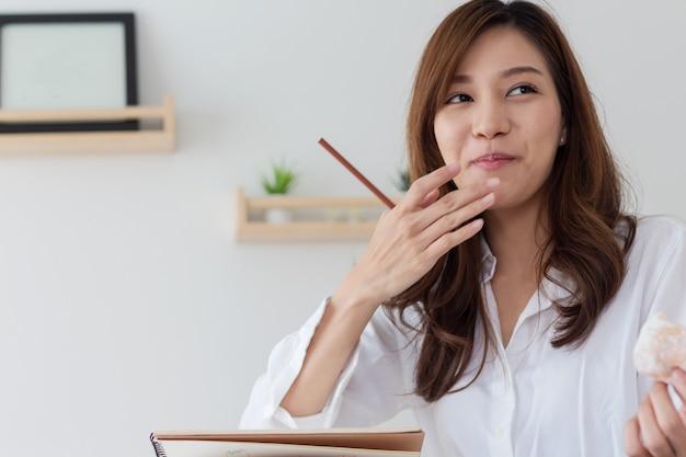 아시아 여성들은 집에서 일하고 간식을 먹는다