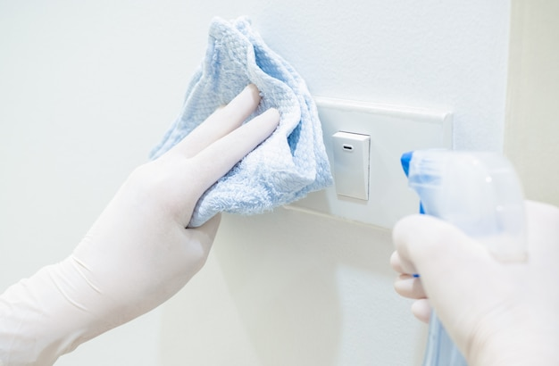 Covid-19の発症時にコロナウイルスの蔓延を防ぐために、アジアの女性はアルコールスプレーまたは防腐剤を使用して、電気スイッチを掃除する自宅で働いています。家事、家からの仕事と社会的距離の概念。