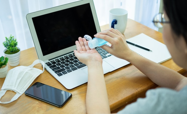 Asian women work at home using notebook, use alcohol gel from bottle to clean hands and prevent spreading of coronavirus during crisis of covid-19.