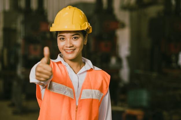 アジアの女性労働者は、良い仕事や仕事のために工場で幸せな笑顔を親指でジェスチャーを示しています。