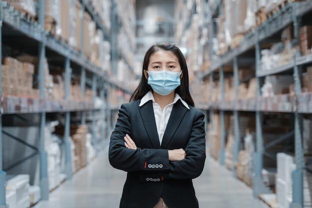 Азиатские женщины-работницы работают в масках во время пандемии covid19 на складе, занимающемся производством промышленных товаров.