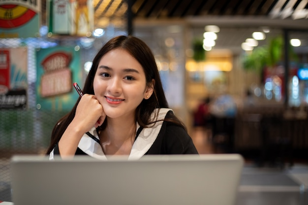 Asian women working and learning online with computer notebook. she smiling and happy