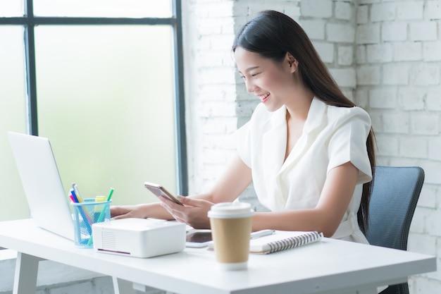 今働いているアジアの女性彼女は自宅の机で、彼女は幸せです。