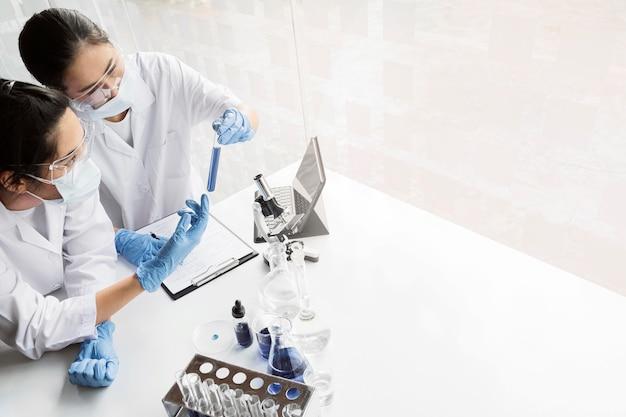 コピースペースで新しい発見のための化学プロジェクトに取り組んでいるアジアの女性