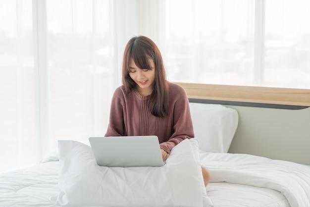 Азиатские женщины, работающие с ноутбуком на кровати дома