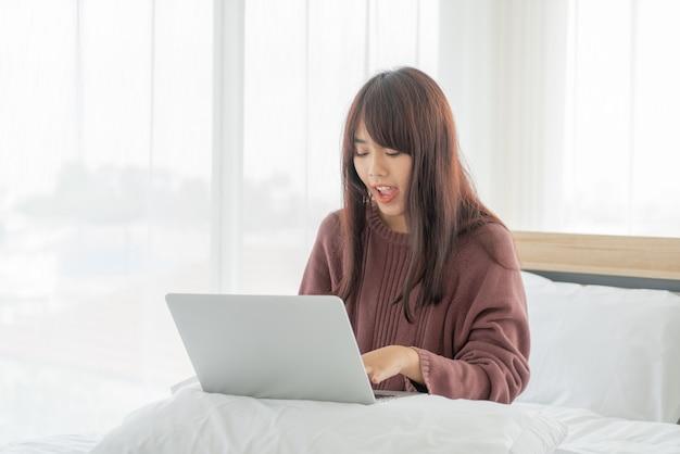 집에서 침대에서 노트북으로 일하는 아시아 여성