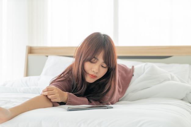 ベッドの上のタブレットを使用してアジアの女性