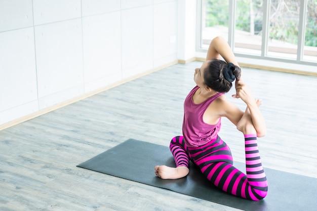 Тренировка йоги азиатских женщин практикуя тренировку надевала розовые одежды и практикует образ жизни и здоровье пригодности раздумья и фитнес пригодности в спортзале
