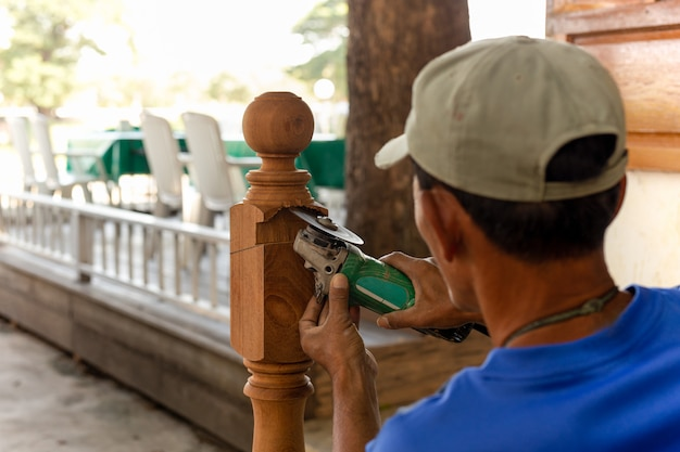 Asian worker cut wooden pole with grinding machine outdoor.