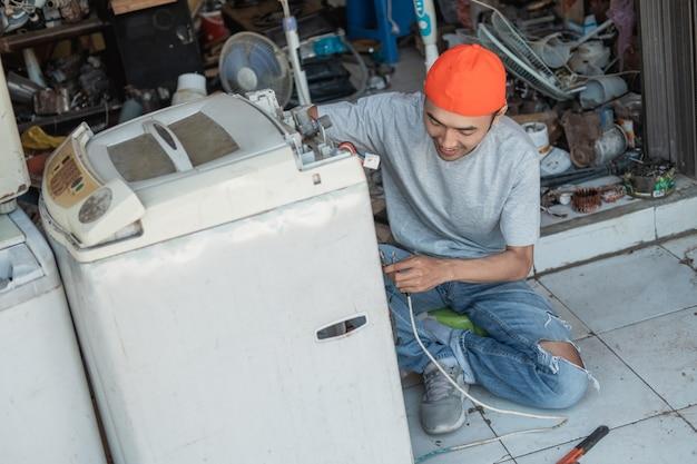 Азиатский рабочий ремонтирует сломанную проводку стиральной машины