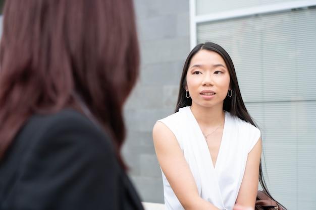 会議をしている彼女の同僚の若い中国の起業家と会話をしているアジアの労働者