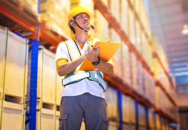 클립보드를 들고 보관 창고에서 재고 관리를 하는 아시아 근로자 재고 확인