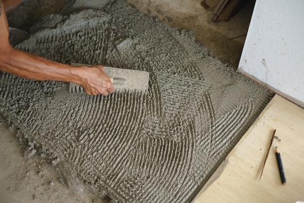 Asian worker laying floor tiles