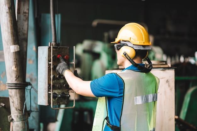 디지털 랩톱 컴퓨터를 사용하는 노란색 헬멧 안전 작업 착용에서 일하는 아시아 노동자 남자.