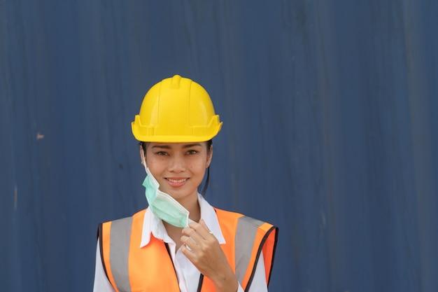 アジアの労働者は彼女のフェイスマスクを保持し、笑顔で青い壁に立っています