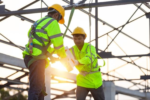 아시아 노동자는 서로에게 벽돌을 나눠주는 안전 장비를 착용합니다. 건설 현장에서 팀워크 개념입니다.