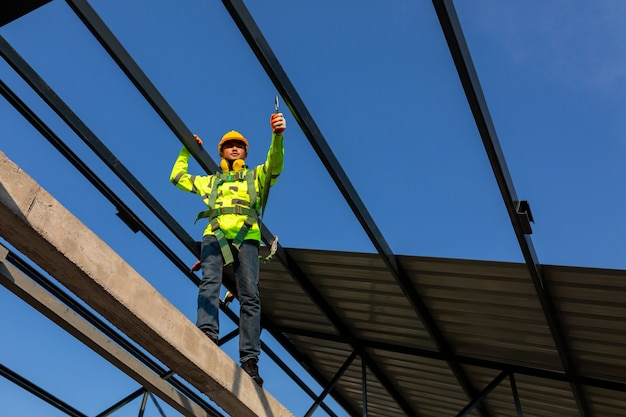 아시아 노동자는 건설 현장에 지붕을 설치하기 위해 안전 높이 장비를 착용합니다. 안전 바디 하네스 용 후크가있는 작업자 용 추락 방지 장치.