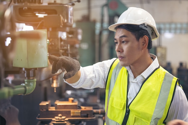 ヘルメットをかぶったアジア人労働者が工場の機械をチェックします。