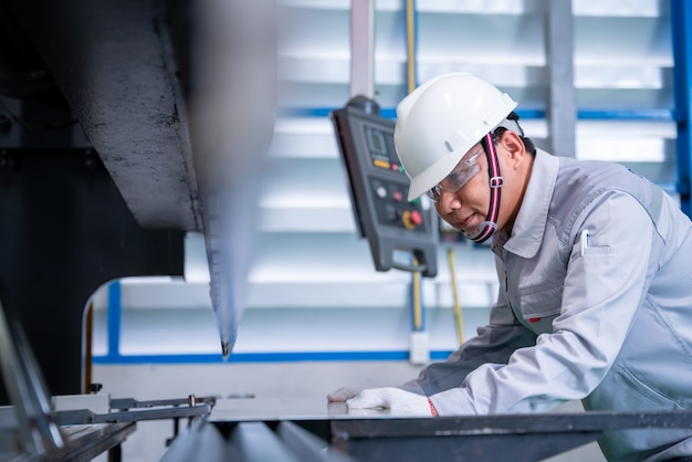 Азиатский рабочий в защитном костюме и установка гидравлической машины