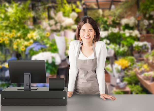 Asian worker with 3d rendering cashier desk in store