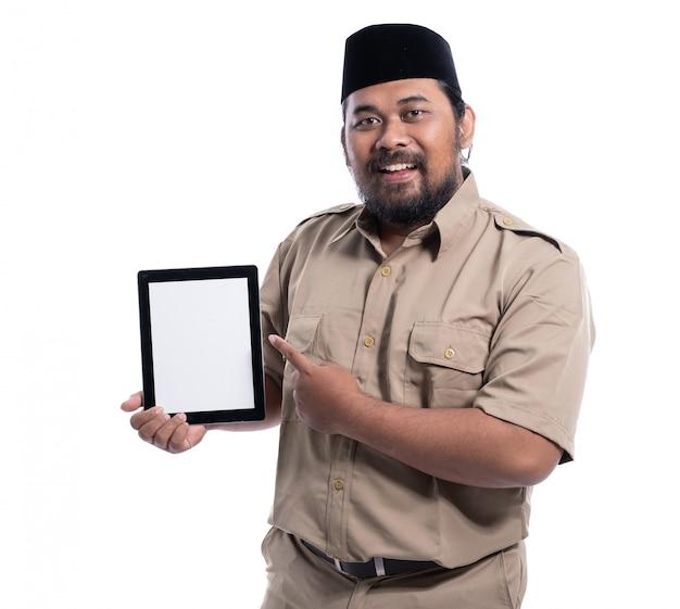 Азиатский работник при коричневая форма представляя к таблетке пустого экрана