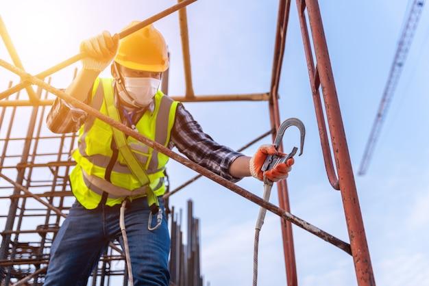 建設現場で建設的な高さ設備で働くアジア人労働者。