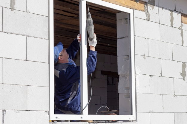 Asian workers install windows to house construction and renovation
