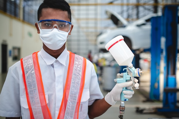 Asian workers stand to hold a spray gun in protective clothing