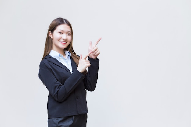 Asian working female who has long hair wears black formal suit with blue shirt