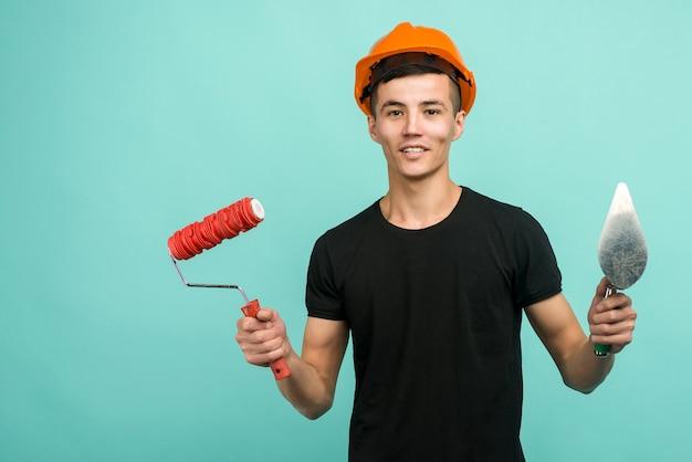 주황색 헬멧에 아시아 일하는 사람은 파란색 배경에 페인트 롤러와 흙손으로 서