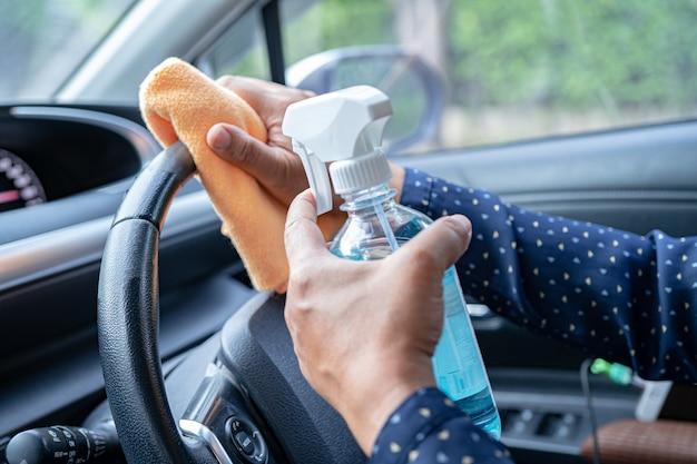 コロナウイルスを保護するためのプレスブルーアルコール消毒ジェルで車の中できれいなアジアの働く女性