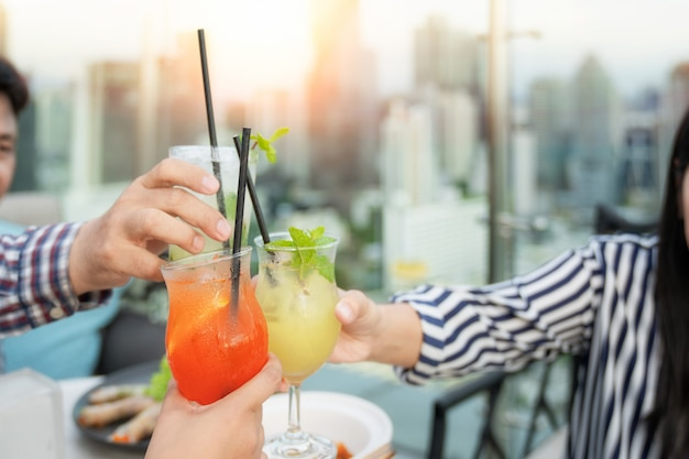 Asian working woman drink mojito cocktail with her girl friend in restaurant on building rooftop with bangkok city background.