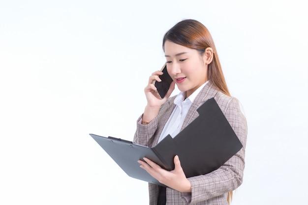 Азиатская работающая женщина в строгом костюме с белой рубашкой звонит по телефону и открывает файл документа