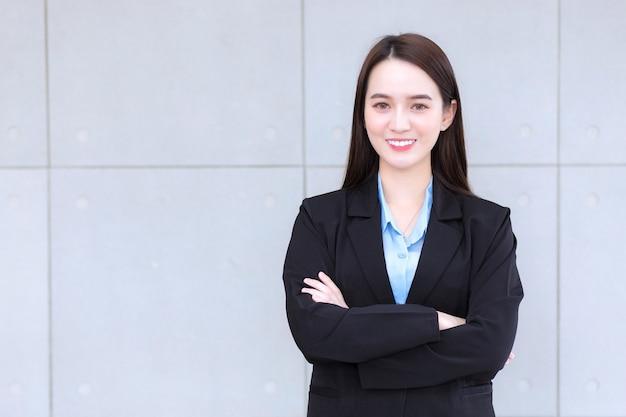長い髪のアジアの働く女性は、腕を組んでいる間、青いシャツを着た黒いフォーマルなスーツを着ています