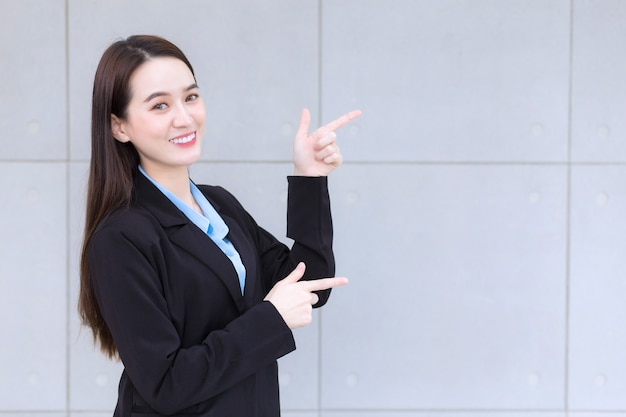 Asian working woman who wears black suit smiles happily is pointing hand to present something
