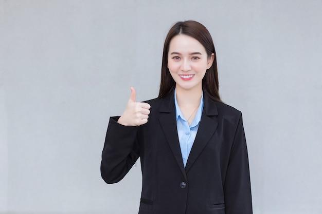 검은 양복을 입은 아시아 일하는 여성이 서서 좋은 사인을 하는 동안 미소를 짓고 있다
