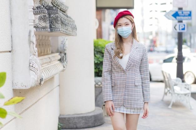 의료용 안면 마스크를 쓴 아시아 여성이 건강 관리 개념으로 거리를 걷고 있다