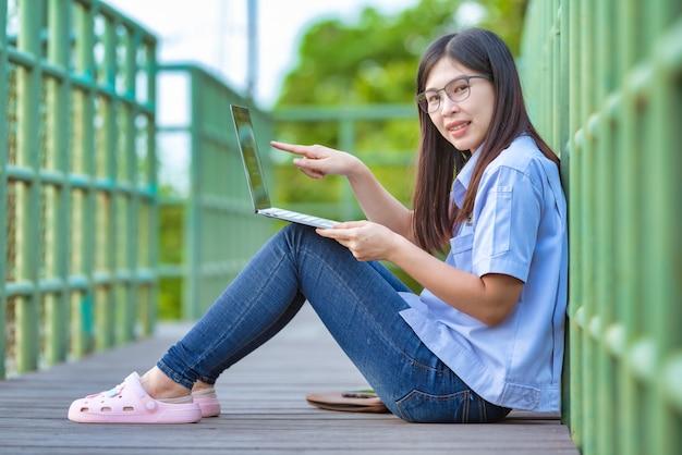 스마트 폰 및 노트북 현대적인 라이프 스타일을 사용하는 공공 공원에서 아시아 일하는 여성, 집에서 일하는 아시아 일하는 여성