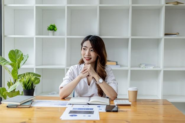 Азиатские работающие женщины сидят в офисе, деловые женщины сидят и ежемесячно проверяют торговые документы, чтобы анализировать и планировать управление продажами, офисное помещение представляет собой дерево за белыми книжными полками и письменными столами.