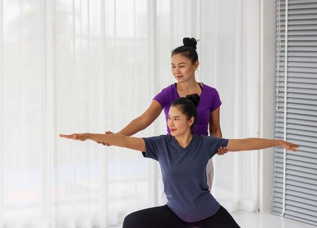 アジアのヨガ教師は、ジムで生徒に1対1で健康的で強いことを教えます。