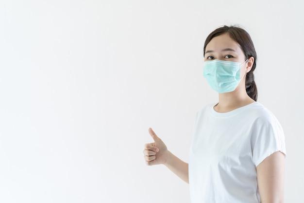 インフルエンザとウイルスを保護するために彼女の顔に防護マスクを身に着けているアジアの若い魅力的な女性。