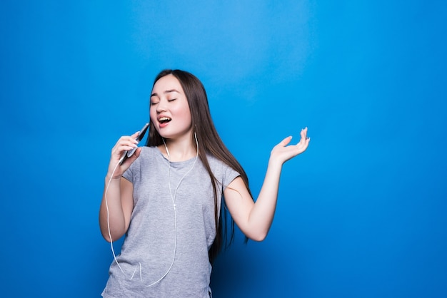 青い壁に分離された電話で歌うヘッドフォンを持つアジアの若い魅力的な女性