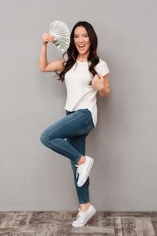 돈을 들고 아시아 젊은 아름 다운 행복 한 여자