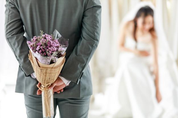 シースルーレースのベールと白いウェディングドレスのアジアの若い美しい幸せな長い髪の花嫁は、ドレッシングルームで驚きに後ろに花の花束を隠す灰色のスーツの新郎を待って笑顔に座っています。