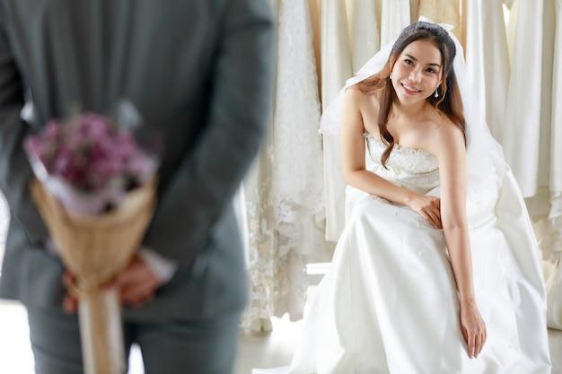 透けて見えるレースのベールが付いている白いウェディングドレスのアジアの若い美しい幸せな長い髪の花嫁は、ドレッシングルームで驚きに後ろに花の花束を隠す灰色のスーツの新郎を待って笑顔に座ります。