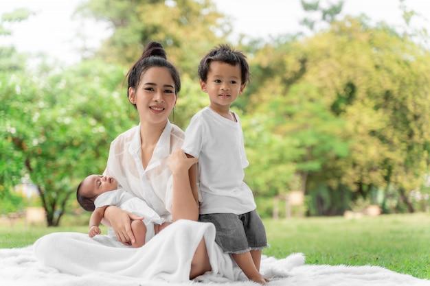 아시아 젊은 아름다운 어머니와 그녀의 아이들, 새로 태어난 아기 소녀와 소년 녹색 잔디에 앉아