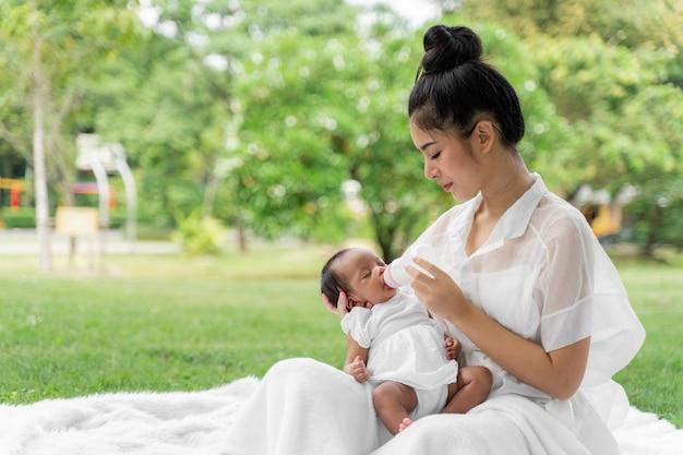 Азиатская молодая красивая мать, держащая своего новорожденного, спит и чувствует с любовью и нежно трогает, а затем сидит на зеленой траве в парке